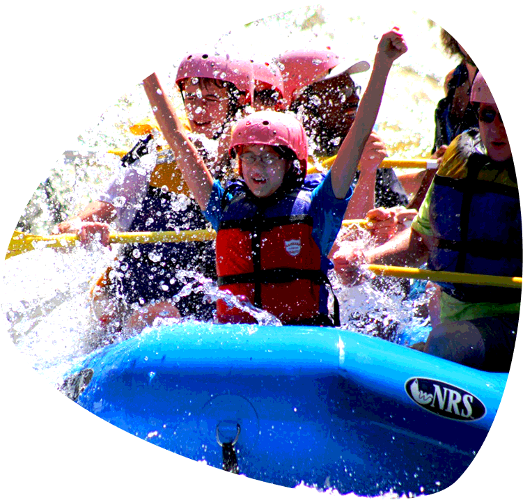 Children enjoying a lower Pigeon River rafting trip in the Smoky Mountains. Child is center of the photo with hands raised in excitement. The raft is hitting a rapid and water is splashing everywhere. Others in the group show expressions that range from laughter to fear and excitement.
