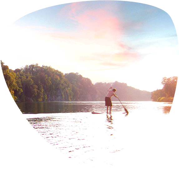 Male and female riding stand up paddle boards (SUP) on Douglas Lake.
